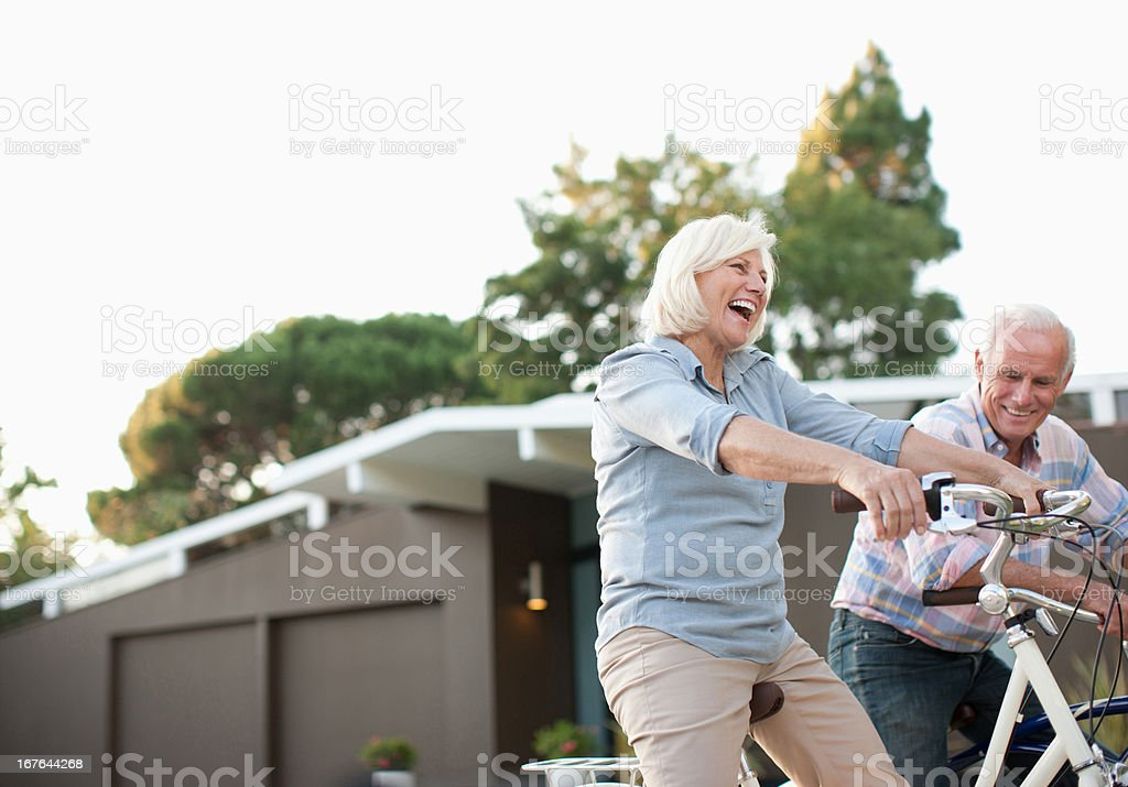 Older couple riding bicycles together stock photo
