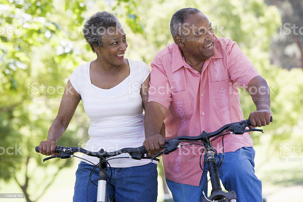 Older couple riding bikes in park stock photo