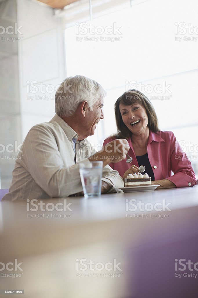 Older couple sharing dessert in cafe stock photo