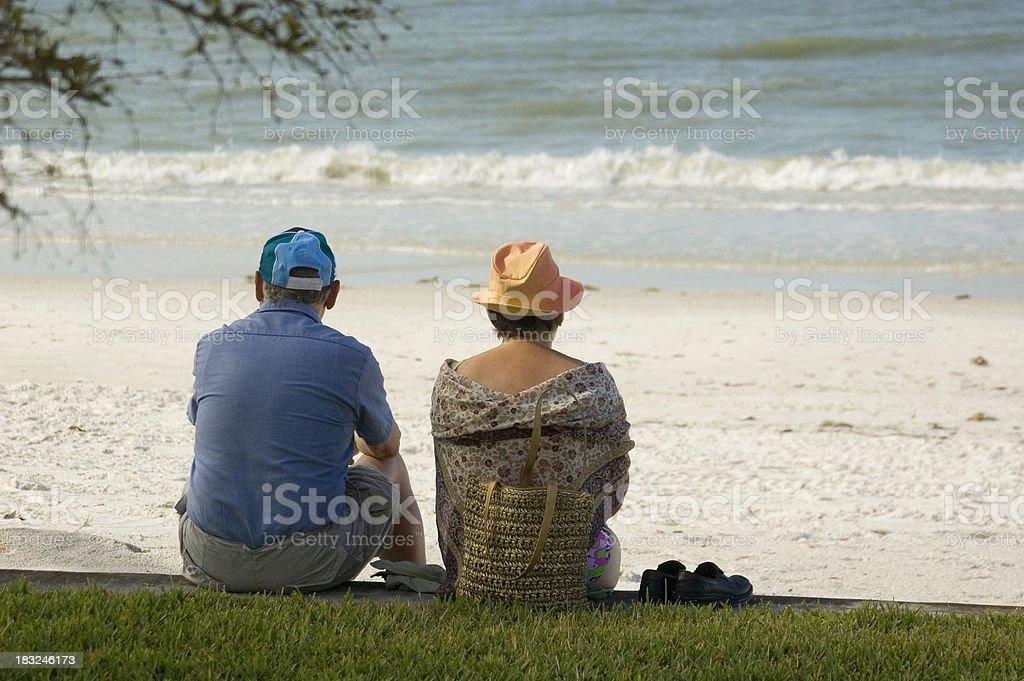 Older couple sit on beach royalty-free stock photo