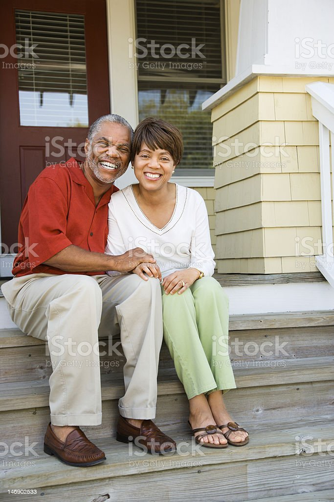 Older couple sitting outside on their front porch steps stock photo
