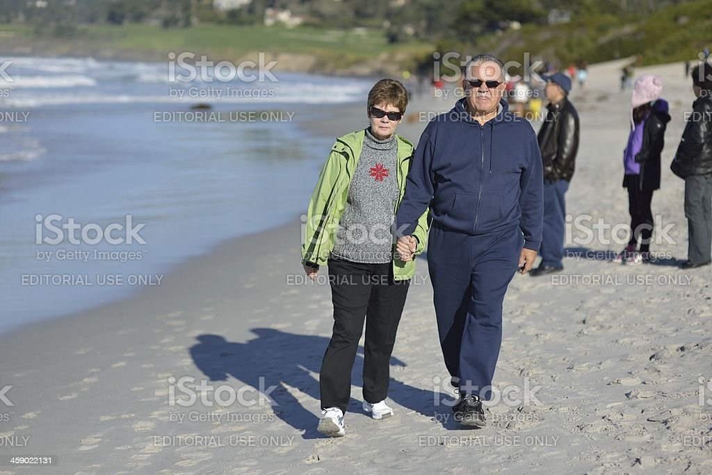 Older couple walking on the beach royalty-free stock photo