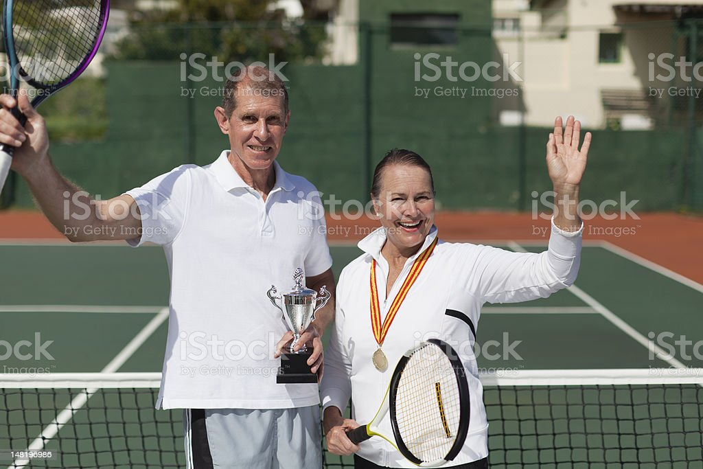 Older couple with trophy on tennis court stock photo