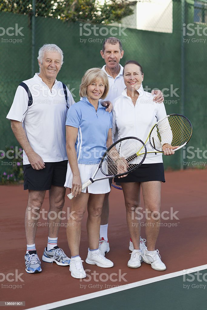 Older couples standing on tennis court royalty-free stock photo