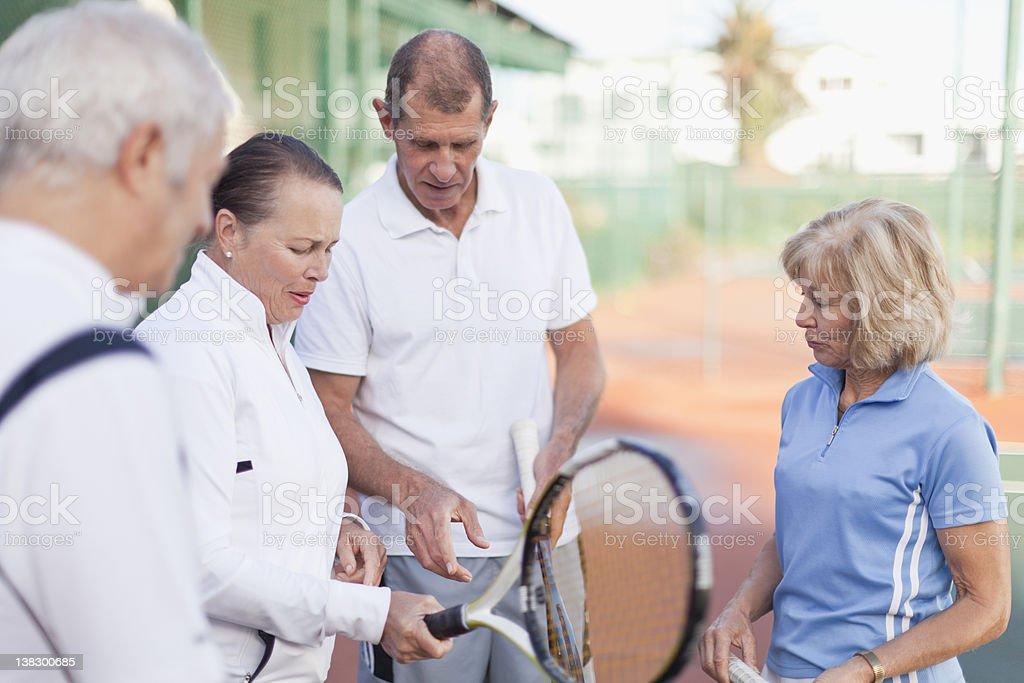 Older couples talking on tennis court stock photo