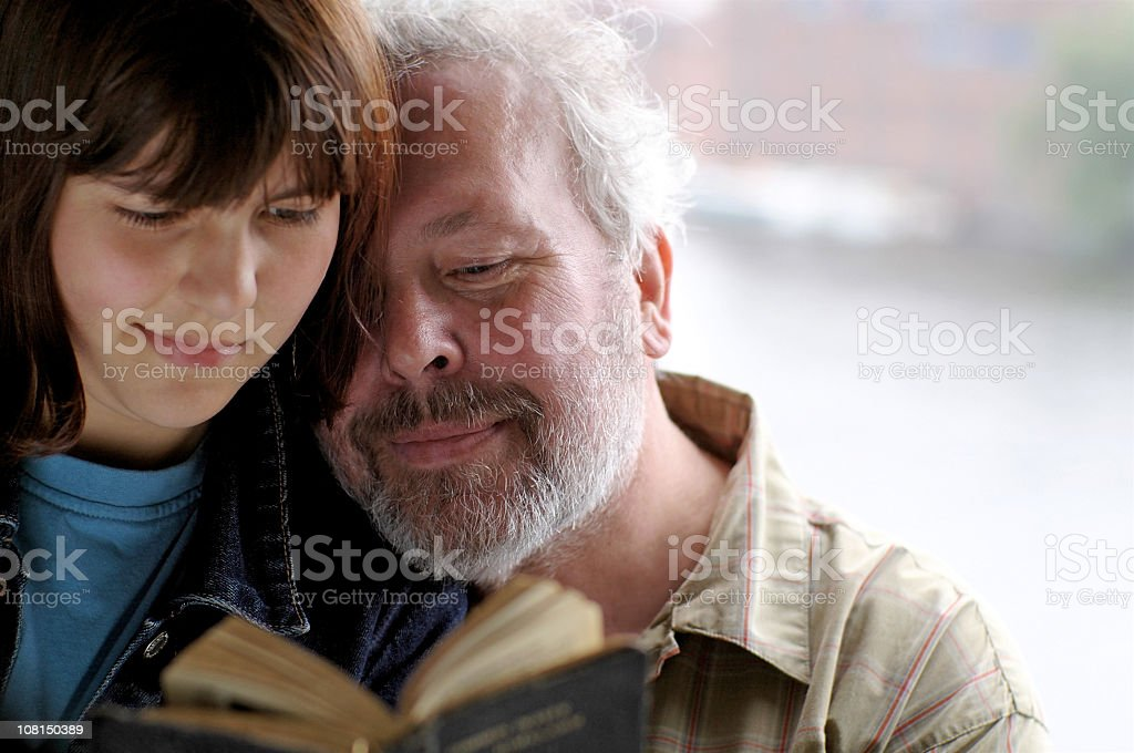 Older Father and Daughter Reading from Vintage Book Together stock photo