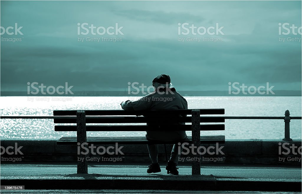 Older gentleman reminiscing on the twilight years at the sea stock photo