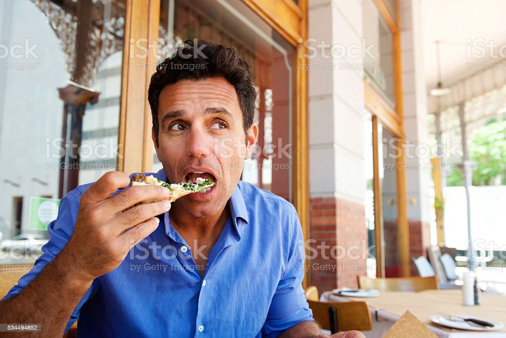Older handsome man eating pizza at outdoor restaurant stock photo