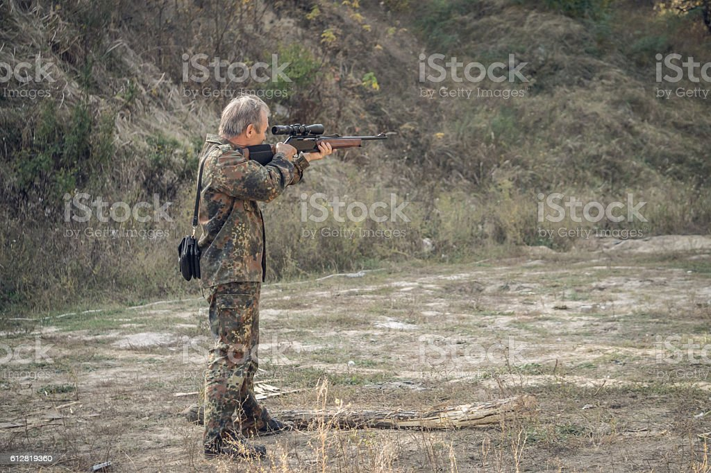 Older hunter with a hunting rifle stock photo