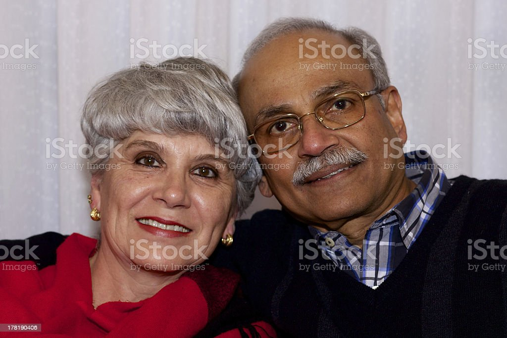 Older inter-racial couple, cheek-to-cheek, all smiles royalty-free stock photo