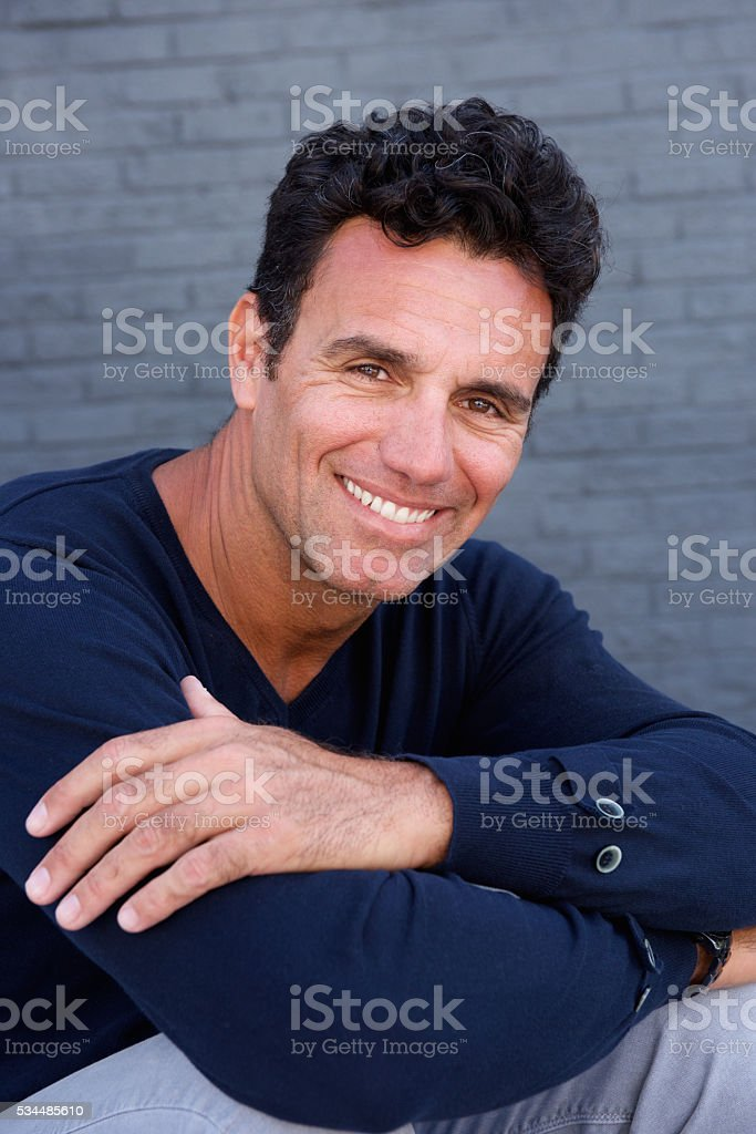 Older male fashion model sitting by gray wall stock photo