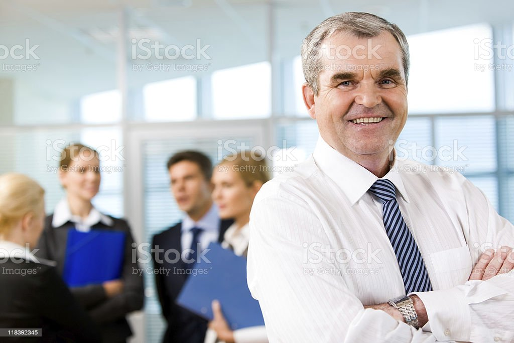 Older male leader of a business team in the foreground royalty-free stock photo