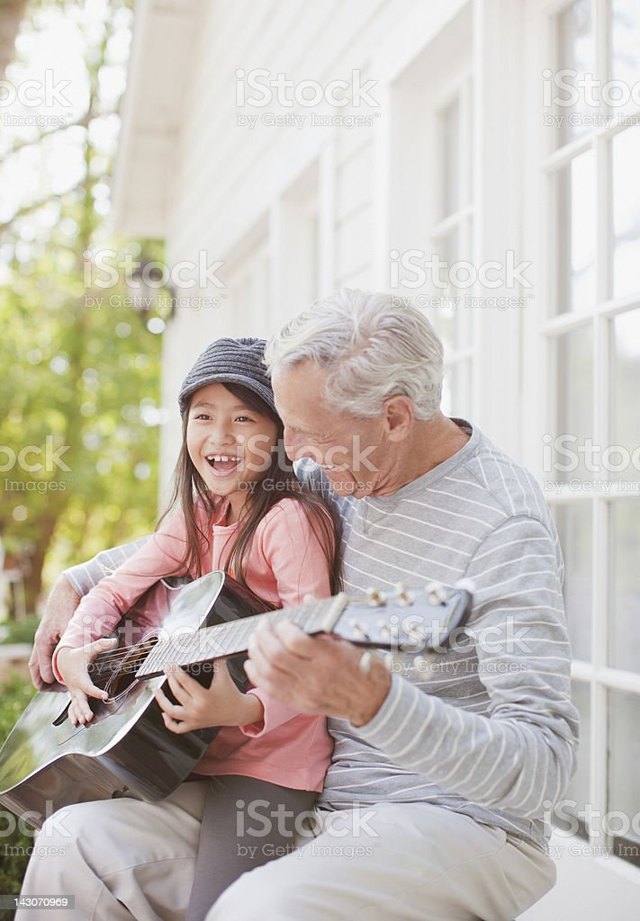 Older man and granddaughter playing guitar stock photo