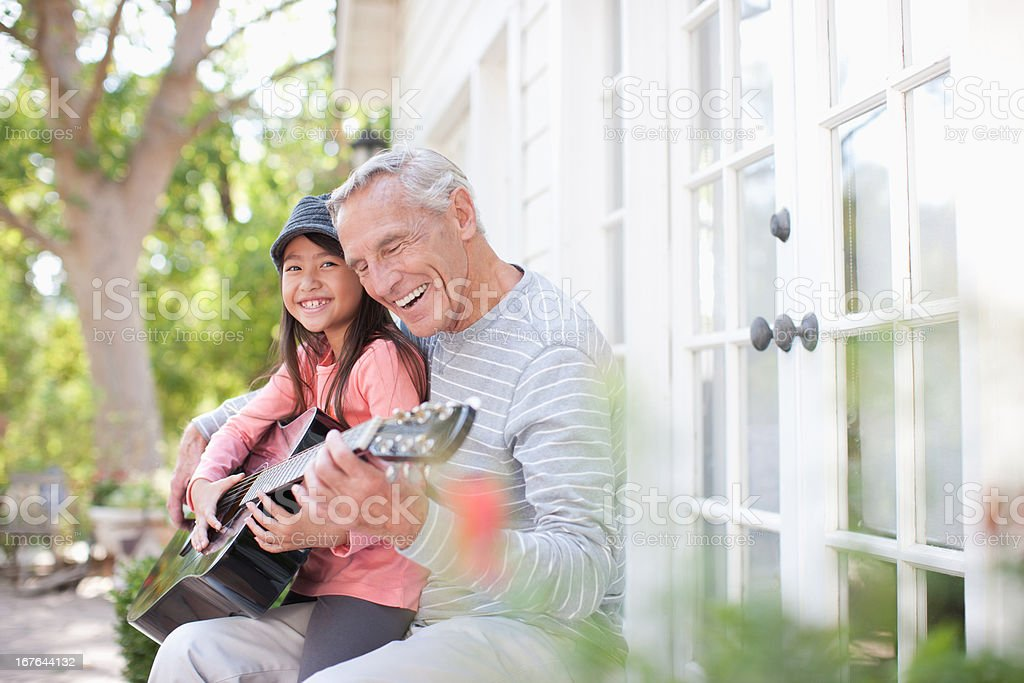 Older man and granddaughter playing guitar royalty-free stock photo