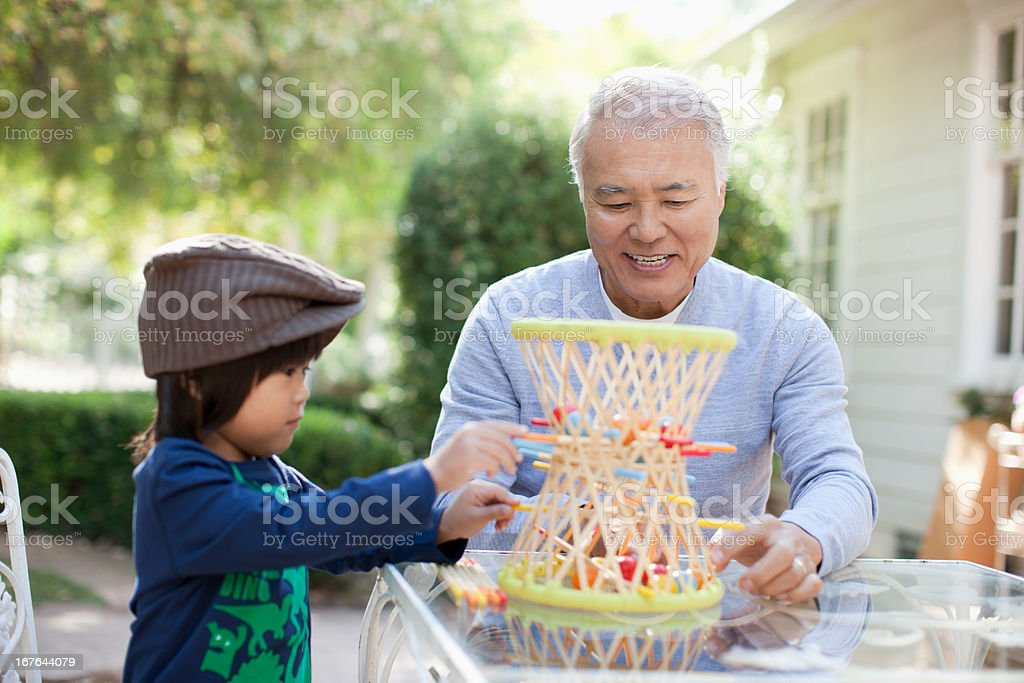 Older man and grandson playing outdoors royalty-free stock photo