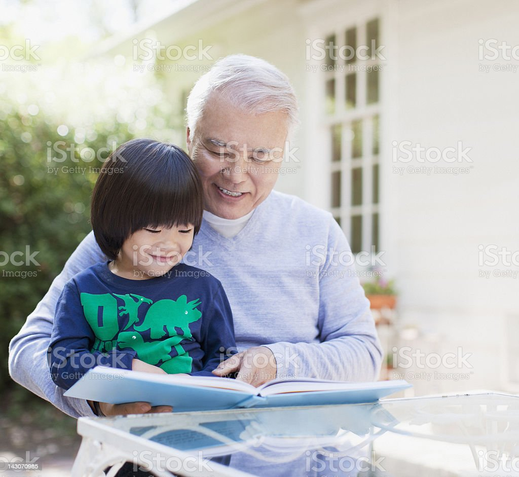 Older man and grandson reading together royalty-free stock photo
