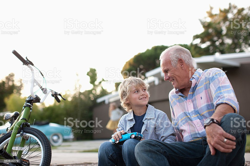 Older man and grandson sitting together royalty-free stock photo