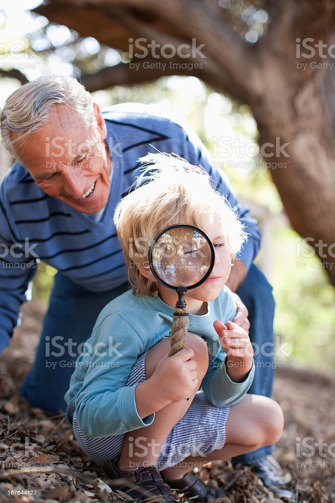 Older man and grandson using magnifying glass royalty-free stock photo