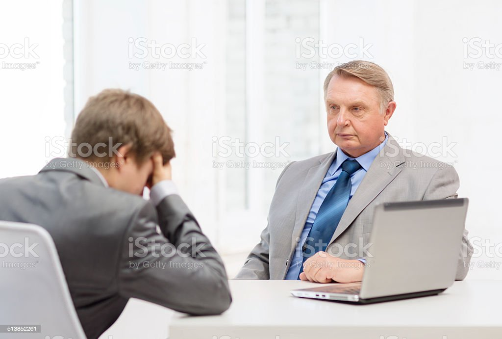 older man and young man having argument in office stock photo