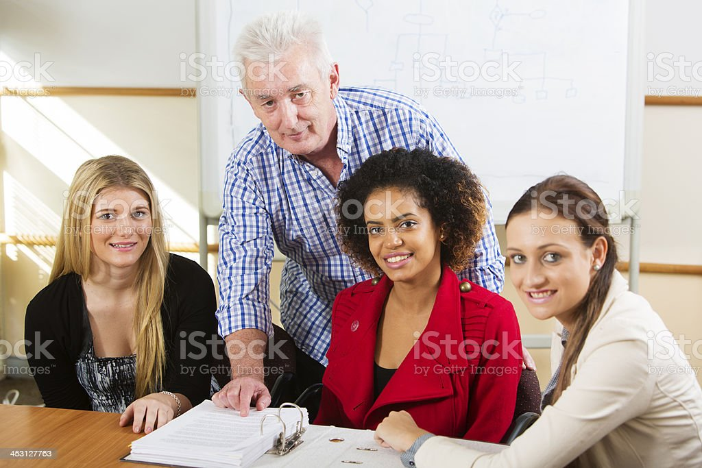 Older Man and Younger Women at Work royalty-free stock photo