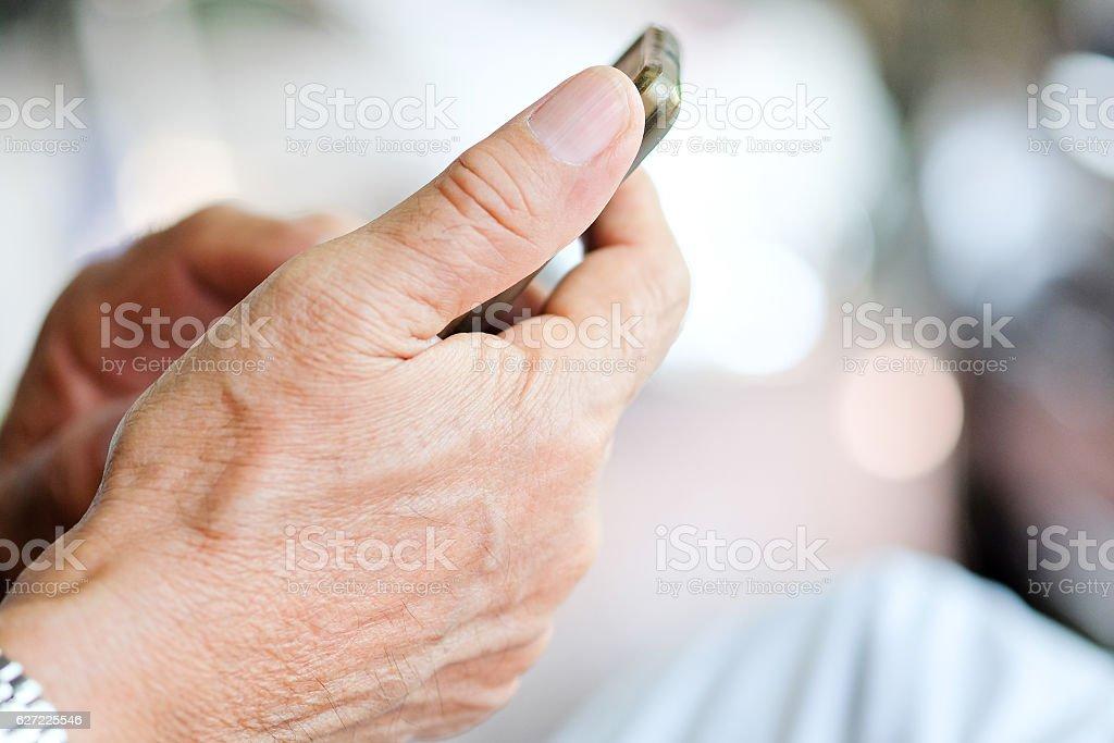 older man checking his phone stock photo