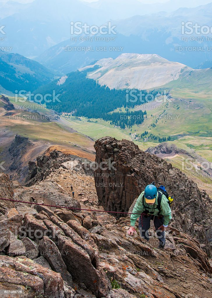 older man climbing with rope extreme vertical rush stock photo