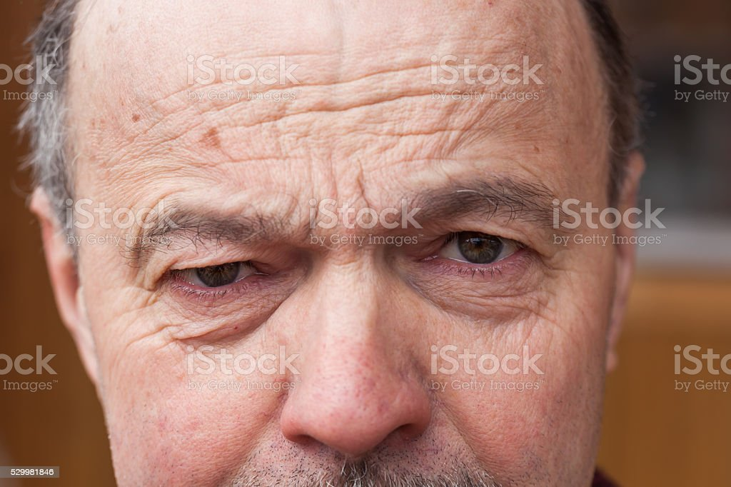 older man frowned. stock photo