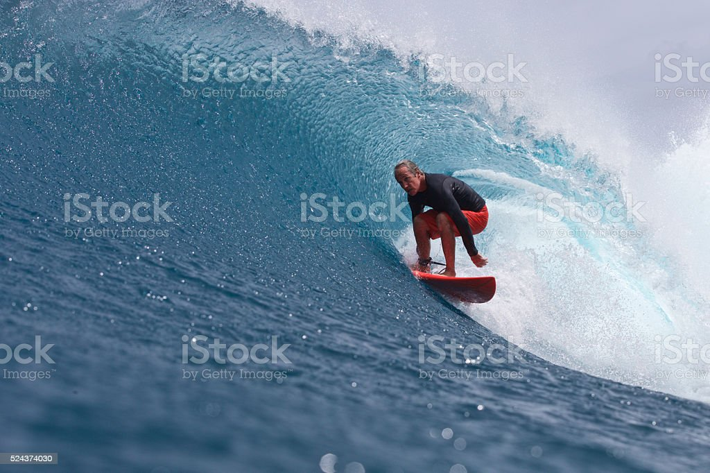 Older man gets barreled on a wave in style stock photo