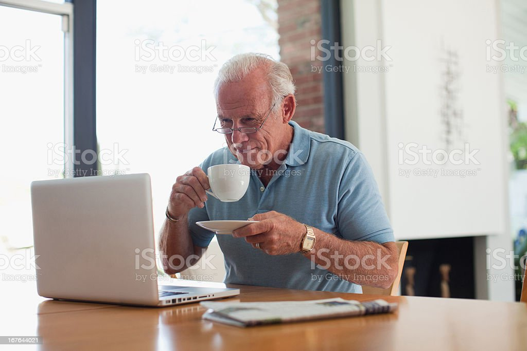 Older man having cup of coffee indoors royalty-free stock photo
