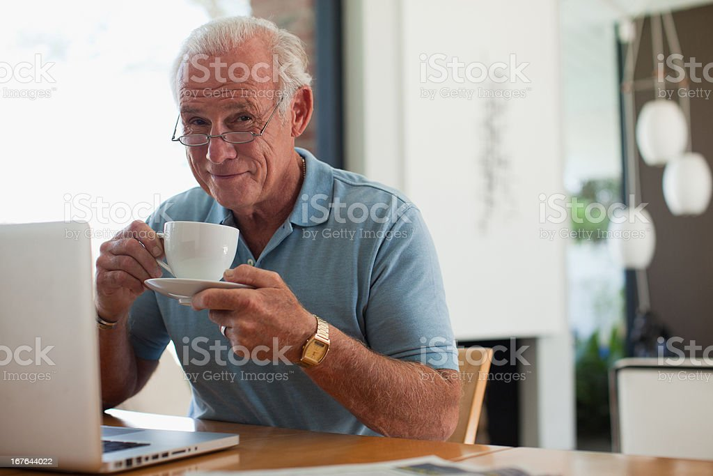 Older man having cup of coffee indoors stock photo