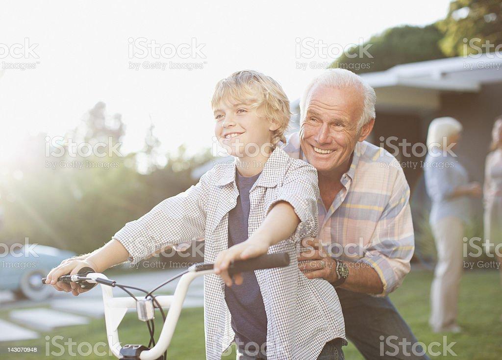 Older man helping grandson ride bicycle royalty-free stock photo