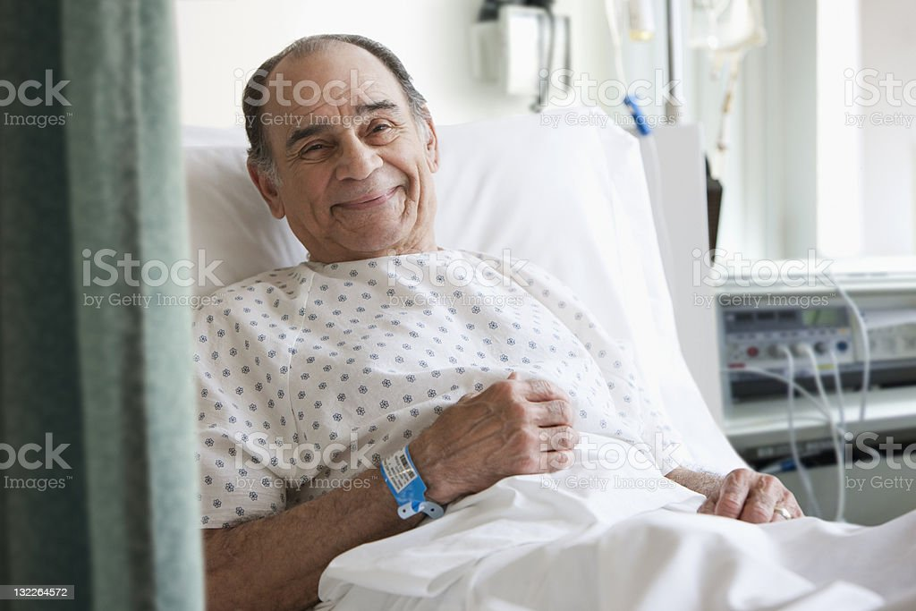 Older man in hospital bed stock photo