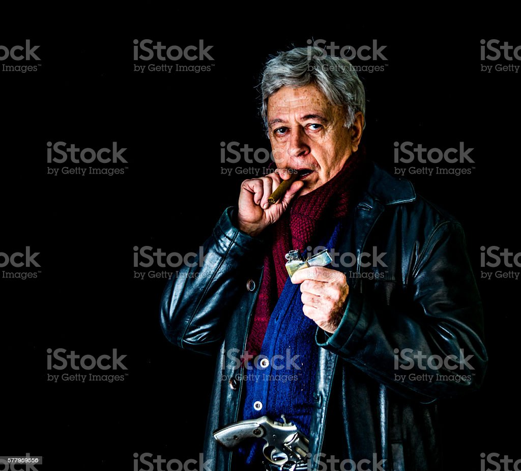 Older man in leather jacket with gun, cigar, and lighter stock photo