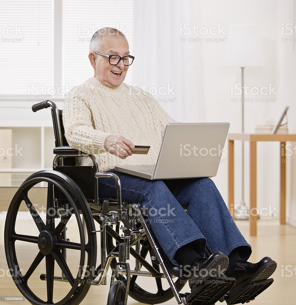 Older man in wheelchair shopping on Computer with credit card royalty-free stock photo
