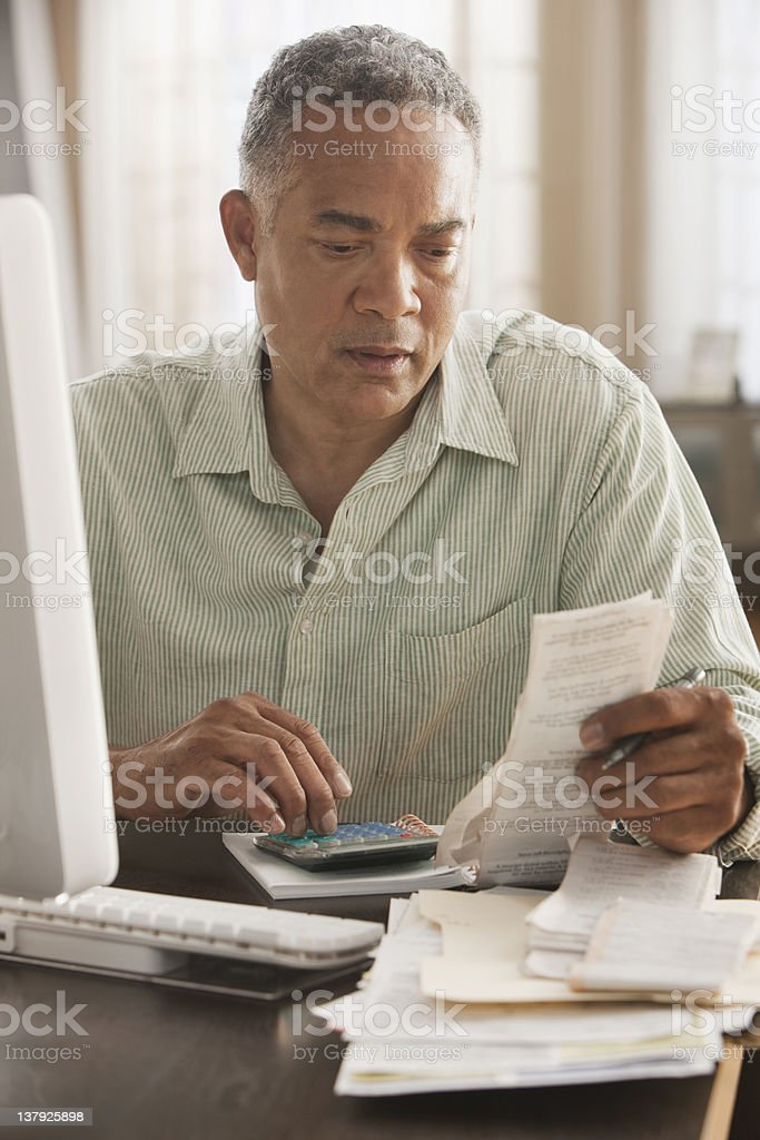 Older man looking at receipts stock photo