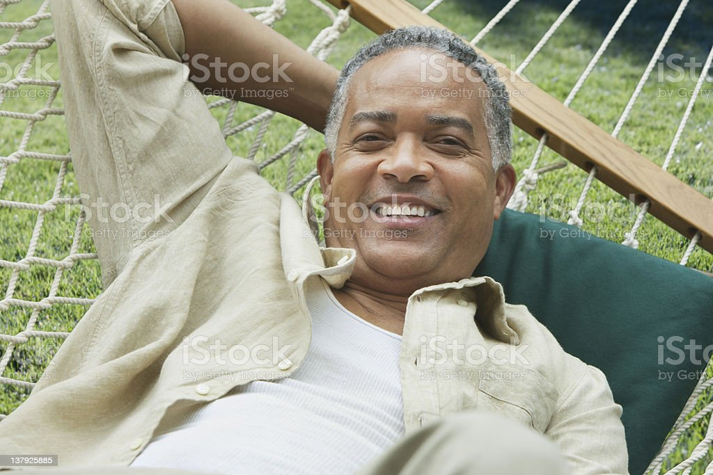 Older man lounging on a hammock royalty-free stock photo