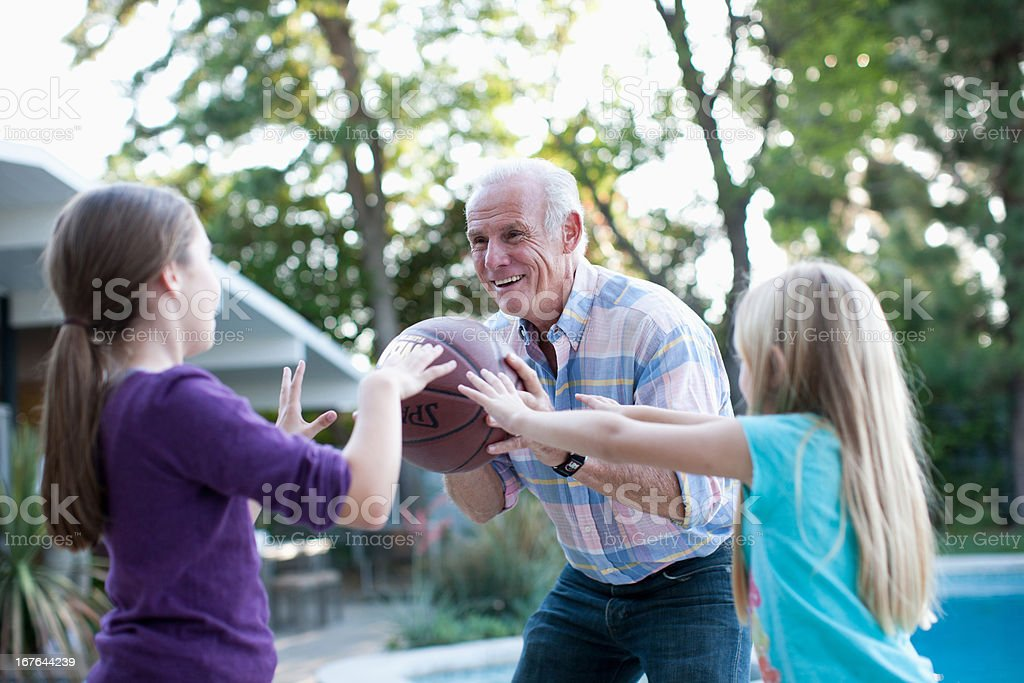 Older man playing basketball with granddaughters stock photo