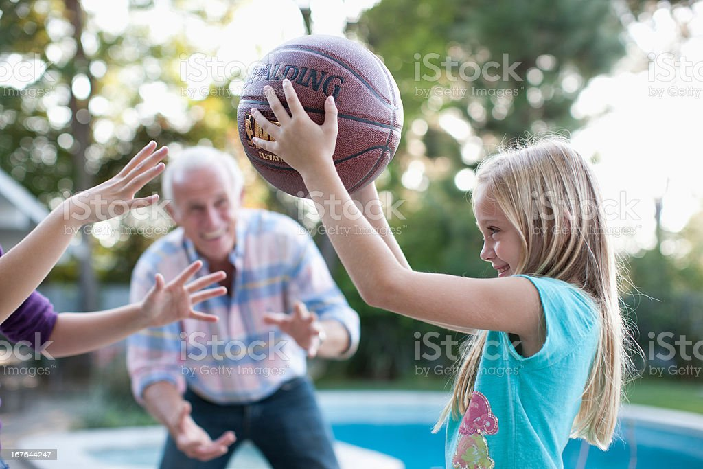 Older man playing basketball with granddaughters royalty-free stock photo