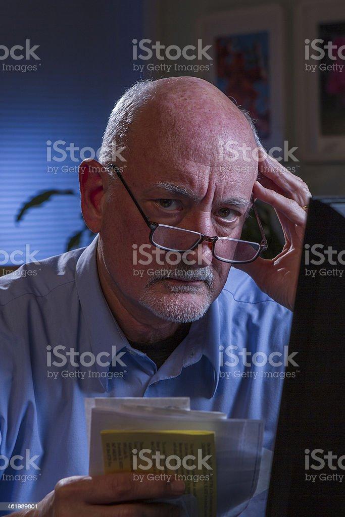 Older man stares at camera, paying bills online stock photo