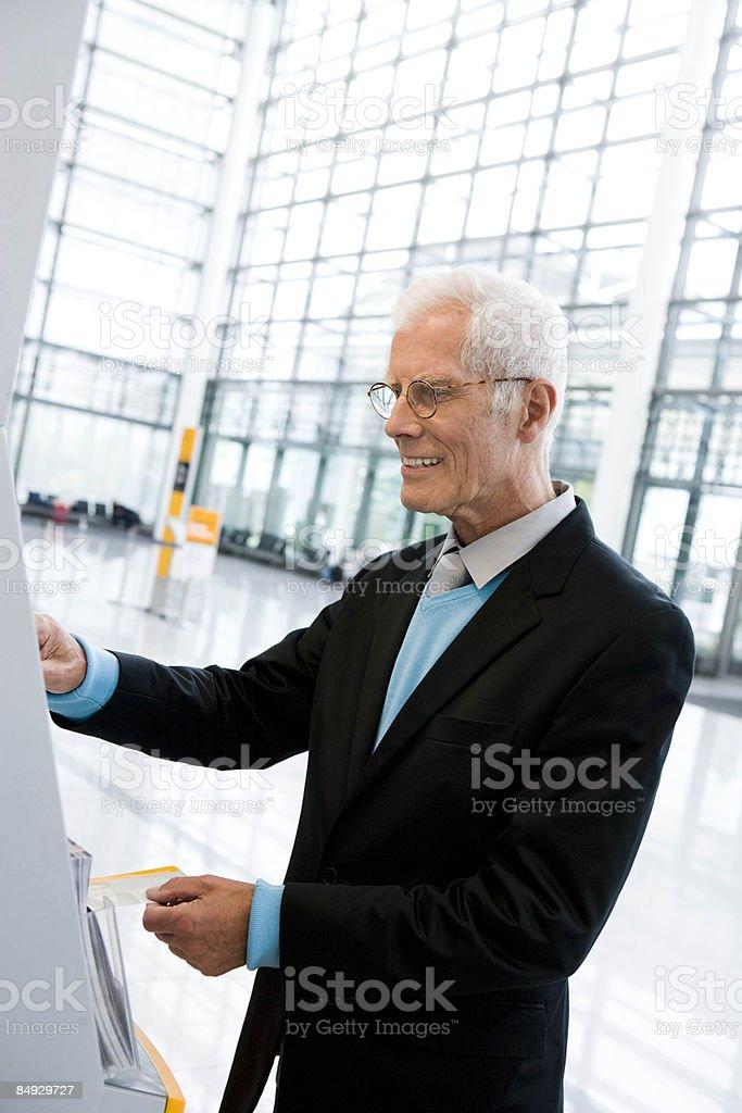 Older man using boarding computer stock photo
