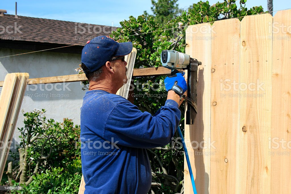 Older man using power tools to build a wooden fence stock photo