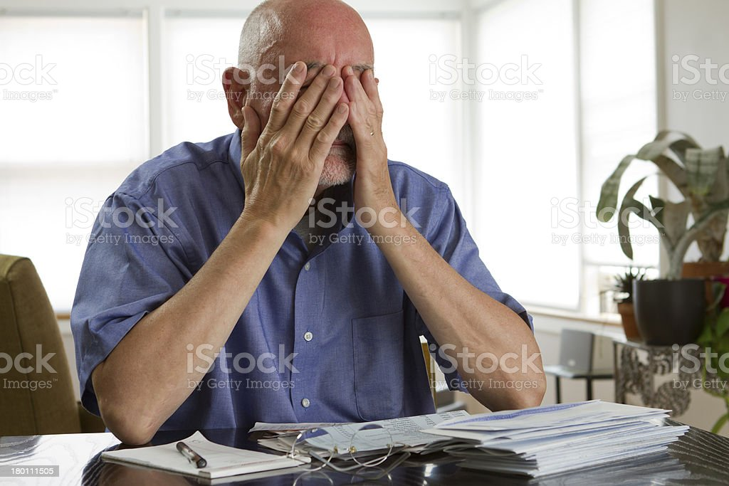 Older man with face in hands while paying bills stock photo