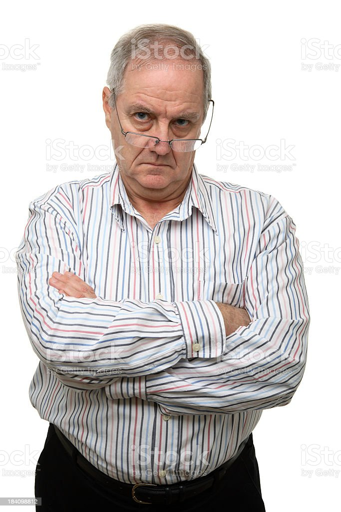 Older man with serious expression, glasses, and crossed arms stock photo