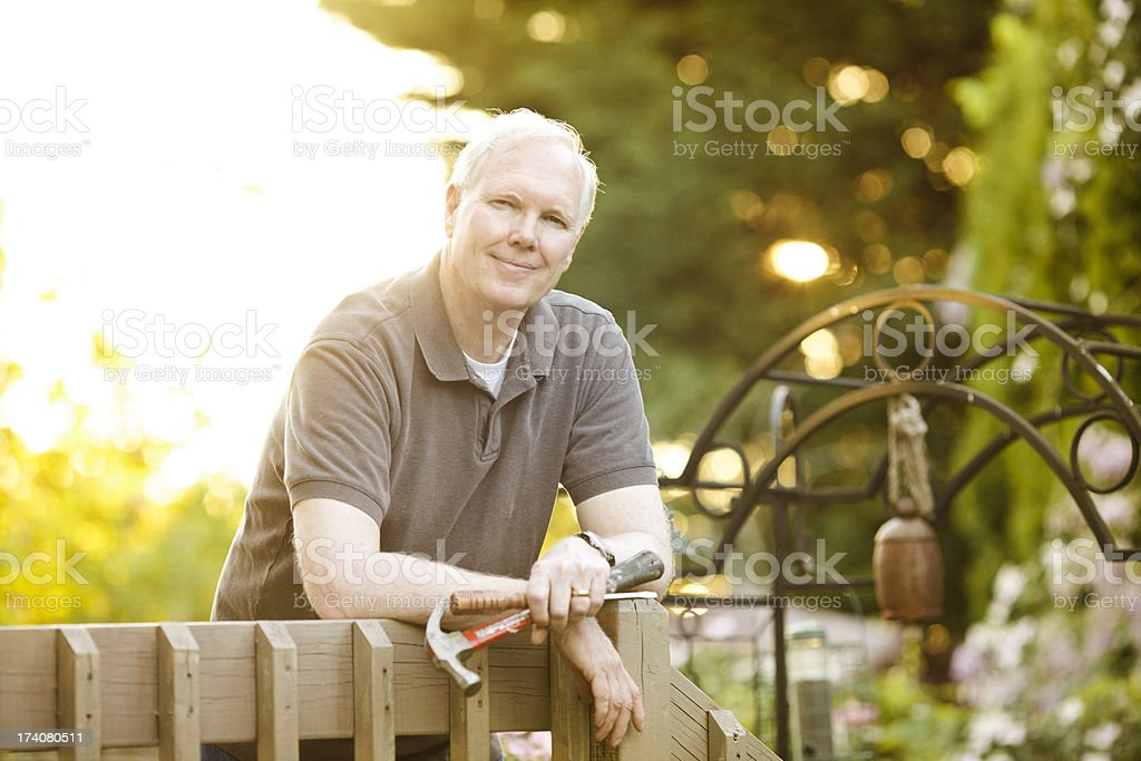 Older man working on his deck. stock photo