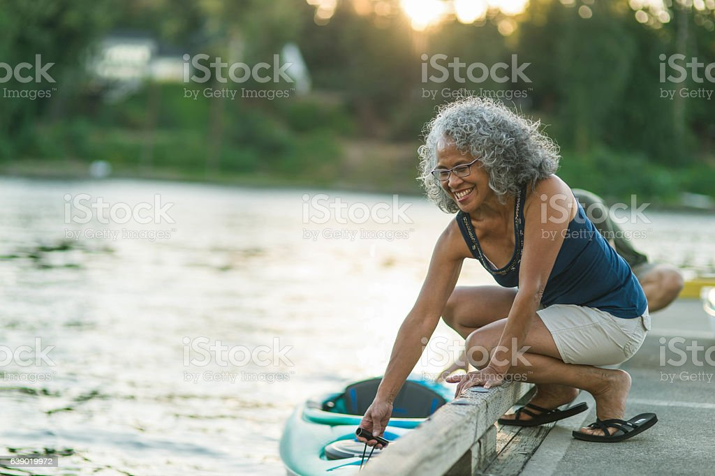 Older mature couple putting kayak in the water together stock photo