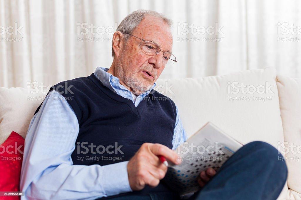 older senior man at home reading enjoying retirement stock photo