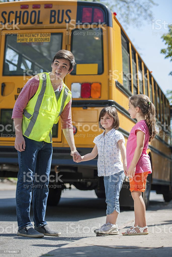 Older Student Crossing Guard Helps Young Elementary Students stock photo
