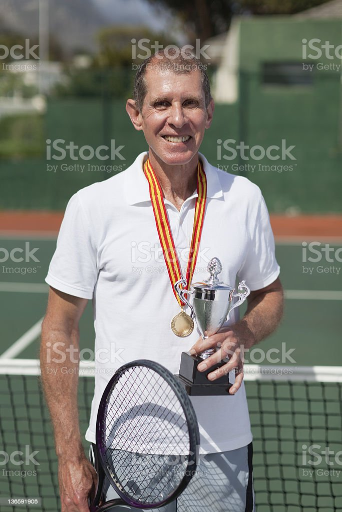 Older tennis player with trophy on court royalty-free stock photo
