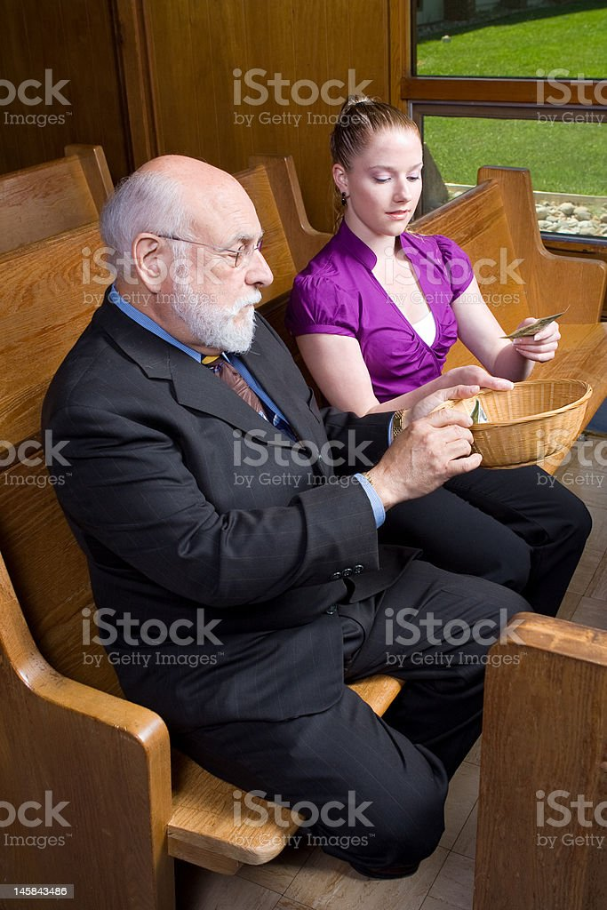 Older White Man Young Woman Donating Money Church Offering Basket stock photo