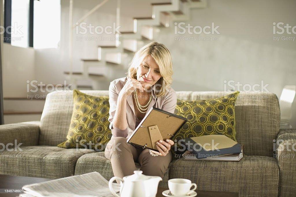 Older woman admiring framed photos stock photo